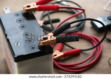 A Car battery with red and black battery Jumper Cables with copper clamps attached to the terminals. Automotive battery on a work desk with tools in background. - stock photo