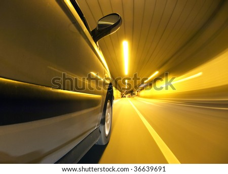 A car driving inside a tunnel in the left lane, overtaking another car - stock photo