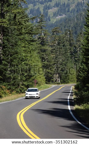 A car driving on a paved road at high elevations in Rainier National Park. - stock photo