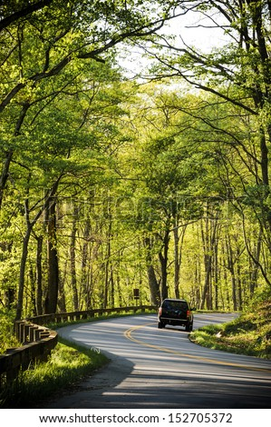 a car driving on a two lane road in the forest - stock photo