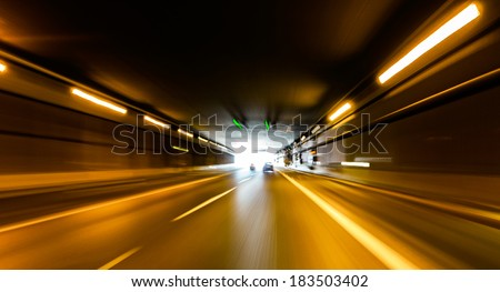 A car going full speed at the end of the tunnel - stock photo