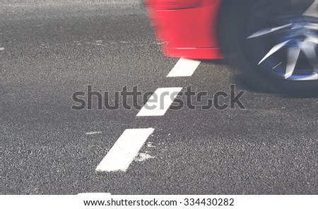 A car is driving through the pedestrian way. This image shows how fast the car is actually moving even in slow speed. Image has a vintage effect applied.