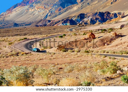 A car meanders along the winding road toward the variegated slopes of Artists Palette in Death Valley, California. Various mineral pigments have colored the volcanic deposits found here. - stock photo