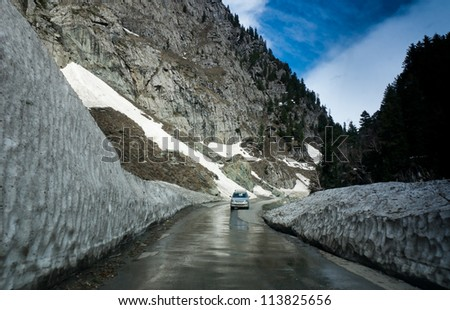 A Car passes through a road as it was cleared of snow in sonamarg , Kashmir India - stock photo
