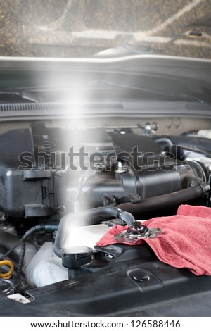 A car's overheated radiator shoots out hot steam. - stock photo