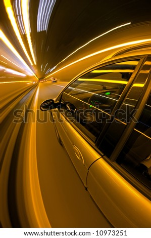 A car, seen from the outside, racing along a motorway at night - stock photo