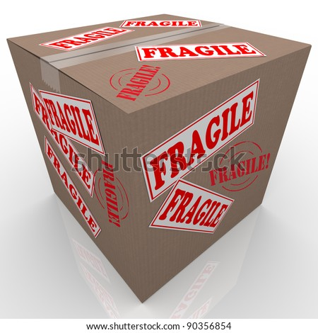 A cardboard box used to ship goods or items with stickers all over it marked Fragile telling the handler or delivery service to handle the package with care - stock photo