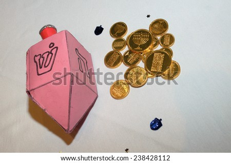 """A cardboard crafted dreidel and stickers along with chocolate """"money"""" for hanukkah. - stock photo"""