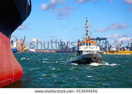 A cargo ship with the assistance of a tugboat in port. - stock photo