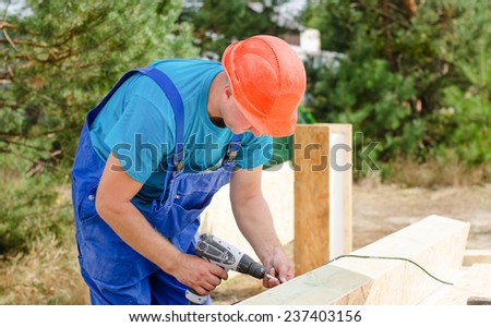 A carpenter in his hardhat and overalls working on a building site using an electric drill to drill a hole in a wooden beam - stock photo