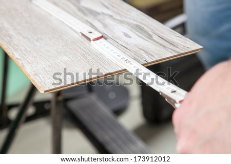 A Carpenter is measuring the laminate. - stock photo