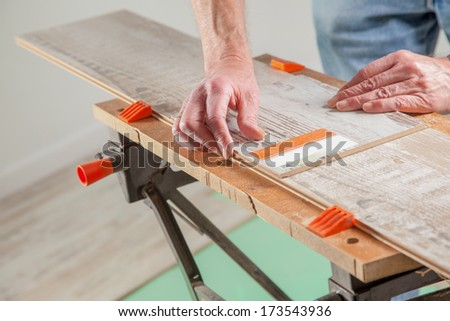 A Carpenter is using a piece of laminate as ruler. - stock photo
