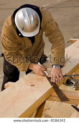 A carpenter laying out the cuts for a stair stringer. - stock photo