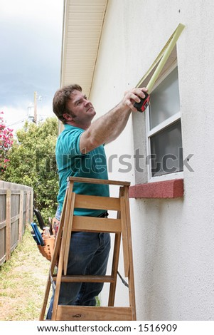 A carpenter or handyman measuring windows for storm shutters. - stock photo