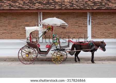 A Carriage with white horse at lampang thailand - stock photo