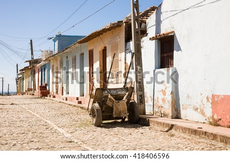 A cart in a historic colonial street with colored houses in Trinidad, Cuba - stock photo