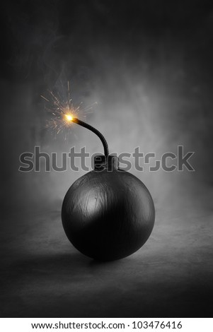A Cartoon-style round black bomb with a burning fuse. - stock photo