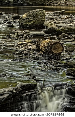 A cascading stream with log and rocks. - stock photo