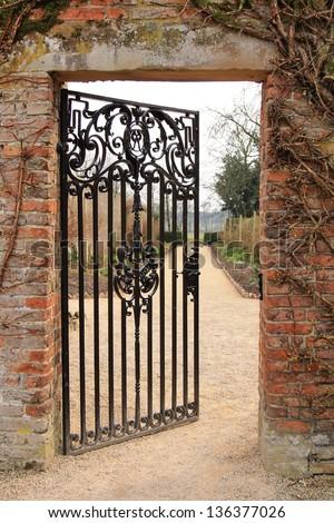A cast iron garden gate standing half open, leading to a garden beyond. - stock photo