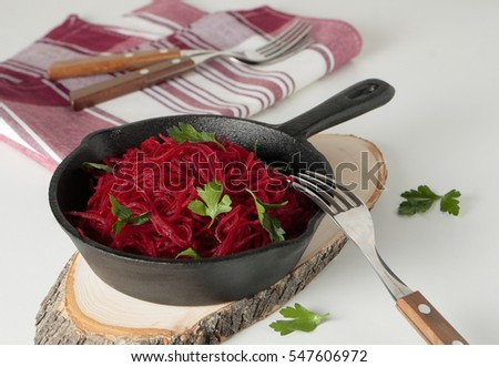 A cast iron pan with braised beetroot and parsley