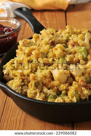 a cast iron skillet with corn bread stuffing with chunks of turkey meat - stock photo