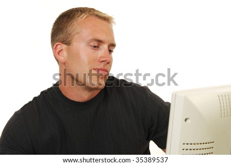 A casual businessman looking at a computer monitor - stock photo