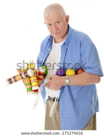 A casual senior adult man looking at the viewer carrying a load of croquet mallets, balls and wickets.  On a white background. - stock photo