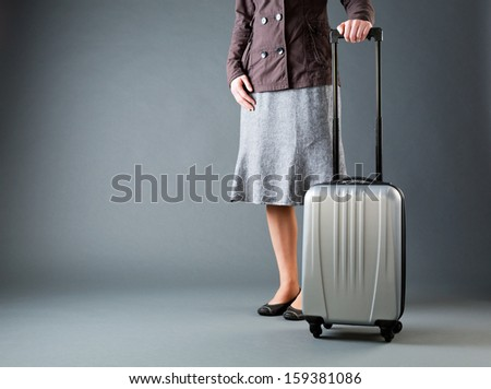 A casually dressed businesswoman with a suitcase on wheels over a gray background.