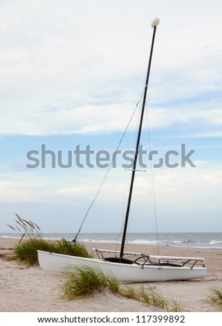 A catamaran boat sitting on the beach waiting for its next voyage. - stock photo