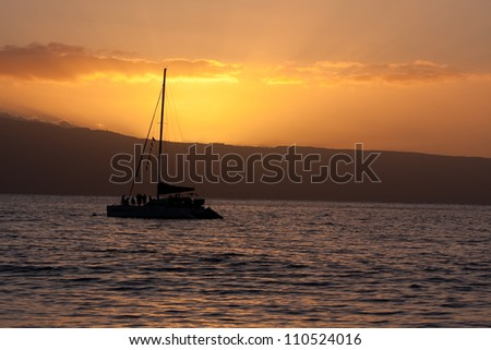 a catamaran silhourtte in the sunset on Maui island in background - stock photo