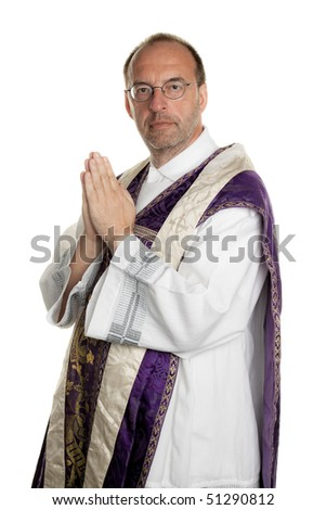 a Catholic priest in prayer in worship - stock photo