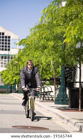 A caucasian businessman riding a bicycle to work, can be used for green or gas savings concept