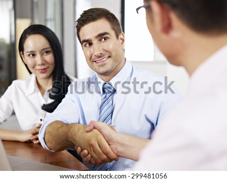 a caucasian businessman shaking hands with his asian partner before meeting. - stock photo