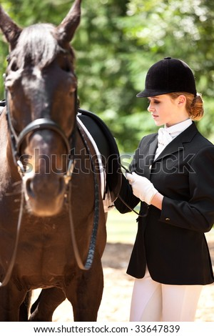 A caucasian girl getting ready for a horseback riding - stock photo