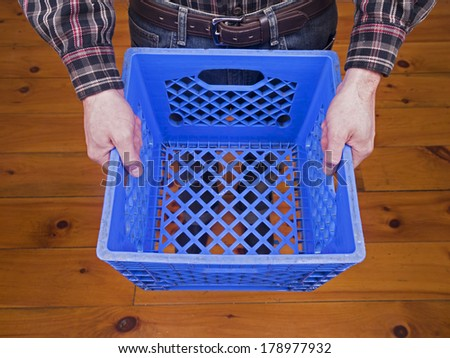 A caucasian male holding a blue crate. - stock photo