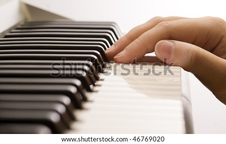 A caucasian male?s hand playing a piano - stock photo