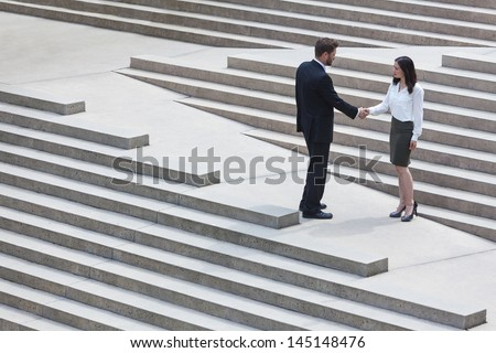 A caucasian man businessman and an Asian woman businesswoman shaking hands on a deal standing on modern city steps