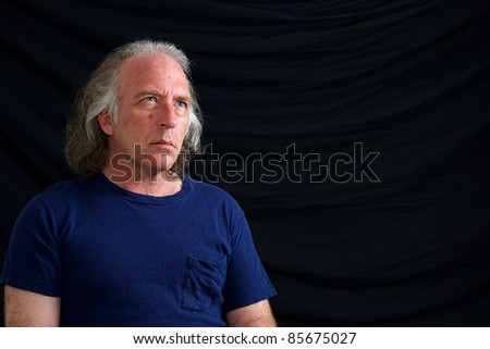 A caucasian man with blue eyes and long white hair is looking up against black background. - stock photo