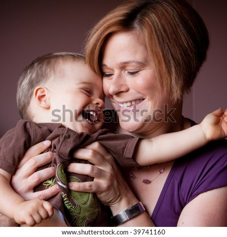 A caucasian mother tickles her child as he giggles uncontrollably