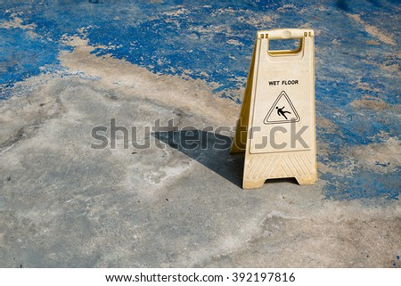 A Caution Sign warns people of a wet floor at swimming pool. - stock photo