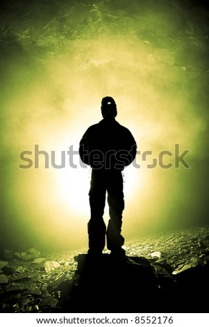 A caver stands on a raised plinth among the debris from recent cave-ins, eerily backlit - stock photo