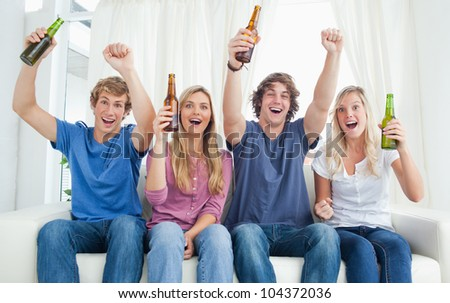 A celebrating group as they look at the camera with beer in their hands - stock photo
