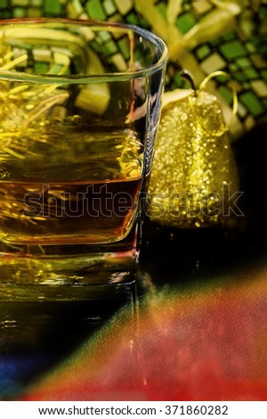 a celebration moment of Christmas or New Year`s Eve where a glass with alcohol is surrounded by decoration ornaments or gifts - stock photo