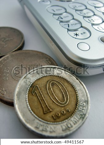 A cellphone keyboard and coins - stock photo