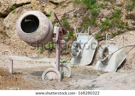 A cement mixerr and two barrows. - stock photo