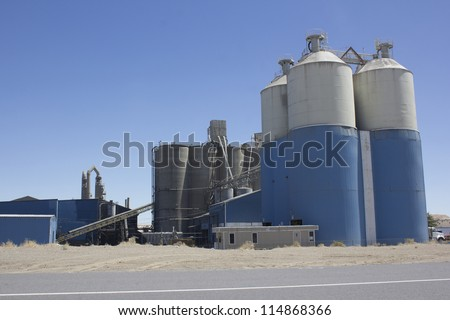 A cement plant with silos and blue skies. - stock photo
