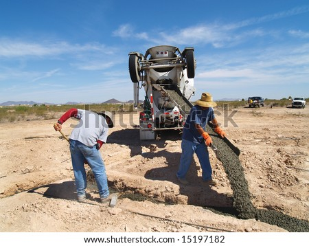 A cement truck is pouring cement into a foundation. A man is pointing the spout into a hole.  Horizontally framed shot.