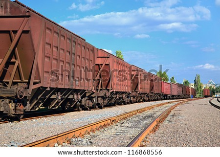 a chain of cargo wagons on a rail road - stock photo