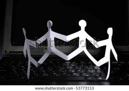 a chain of paper fellows on laptop - stock photo
