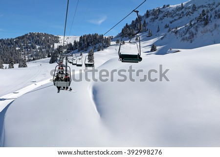 A chair lift transports skiers and snowboarders up a slope in a ski resort at Villars in the Swiss Alps. - stock photo